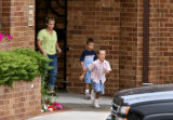A woman and two boys leave a building after being interviewed by Jefferson County Sheriff...