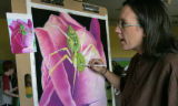Using a photograph of a green spider artisit, Jessa Huebing-Reitinger works on her study for a...