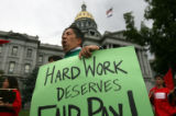 """Hard work deserves fair pay,"" chants John Kefalas, 52, of Fort Collins as he marches..."