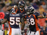 08/19/2006 Denver Broncos linebacker Ian Gold, middle, celebrates with linebackers Nate Webster,...