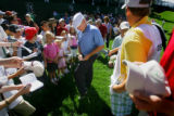 PGA Tour professional Clarence Rose (center, in blue shirt) signs autographs for young fans just...