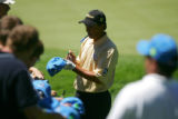American golfer Tom Pernice Jr. signs autographs on hats jsut off the 9th  green during practice...