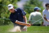 American golfer Nick Watney practices chipping out of a sand bunker on the driving range during...