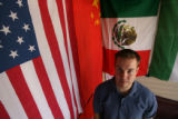DLM00184  Geography teacher Eric Hamlin poses for a portrait in his home with flags from his...