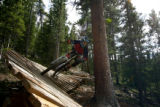 Rocky Mountain Adventure.  A biker races along a wooden construction at Keystone resort.  The wood...