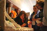 Linda Cordova weeps as she leans towards her nephew, Deion Santistevan's, body as it lays in a...