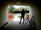 Jim Linden (cq), of Boulder, takes shelter from a rain shower in a tunnel Monday afternoon August...