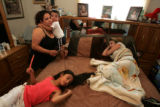 Michelle Venzor, cq, left, holds her son Kenny Venzor, 2, while in her room with daughters Celine,...