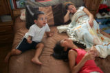 Kenny Venzor, 2, watches cartoons in his parents' room with sisters Celine, cq, 7, and Kenia, cq,...