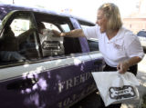 Amy Evans (cq), Sales and Marketing Manager of Morton's Steakhouse, hands a box lunch to a Freedon...