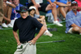 Australian golfer Greg Norman stares at the placement of his chip shot on the 17th green  during...