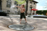 Cooper McCormac, 3, plays in a new fountain at Oak Street Plaza Wednesday afternoon August 30,...