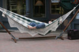 Justin Wagner (cq) takes a rest in one of his hammocks in front of his store, Four Seasons...