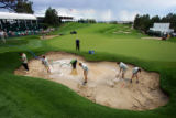 Grounds crew work to empty rain water from a sand bunker on the 18th green after heavy rain...