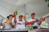Workers at Panda Express sell orange chicken for 2 tickets at the Taste of Colorado at Civic...