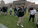 New Colorado head coach Dan Hawkins walks off the field dejected after he started his career with...