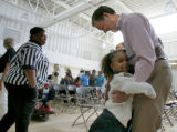Rejonae Thibodeaux, 5 of New Orleans hugs Gov. Bill Owens at a reunion of Katrina evacuees at the...
