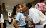Mya Williams, 7, cq, gets a kiss from her mother Jamie Raphael, cq, before she heads in to her...