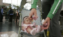 Renee Grinnen (cq) of Aurora removes the shoe of her baby Felicia Aragon, 3 months before going...