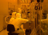 Employees of Intel work on the process of building a disc from which a chip is made.  The process...