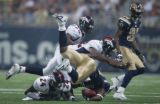 JPM625 St. Louis Rams runningback Steven Jackson is upended by Champ Bailey, #24, Ian Gold, #52,...