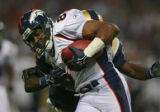 Denver Broncos wide receiver Rod Smith (#80, WR) takes a hit from the St. Louis Rams' Oshiomogho...