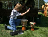 Adam Bierstedt, 10 years old, puts down his flute to play some drums while attending the African...