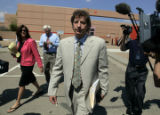 Seth Temin ( younger, light suit) and Steve Jacobson (gray suit, older) walk out of the Boulder...