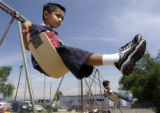 (SHERIDAN, Colo., JUNE 30, 2004)  Saul Pineda swings during recess at  the Early Childhood Center/...