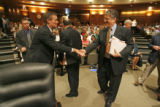 Colorado Gov. Bill Owens, left, shakes hands with Robert Rector, Senior research Fellow from the...