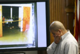 Raul Gomez-Garcia(cq), looks at the floor while standing in front of a interior-view photo of the...