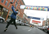 Eric Landauer, 23, makes a leaping catch while enjoying warmer weather at Larimer Square where he...