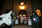 Parishioners sing outside the Holy Family Church during the Posada, an annual procession that...