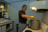 ** season to share** Charles Feely (cq), a resident at New Genesis, stirs soup in the shelter's...