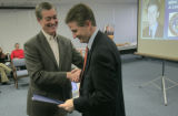 Mike Beasley (cq), the director of the Department of Local Affairs, gets a hand shake from...