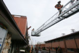 A Denver firefighter runs across a ladder as firefighters clean-up after a blaze at a medical...