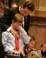 Colorado State Sen. John Evans, (R-Douglas), comforts his son Evan Evans, 13, who started to cry...
