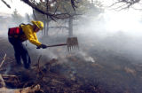 Arvada firefighter  Tim Lile (cq) puts out hot spots near a home north of Hwy 72 and west of Hwy...