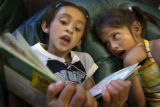 (DENVER, Colo., July 12, 2004) First grade graduates  Aide Marquez,  reads to  Angelica Montes...