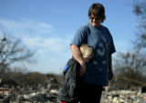 Lauretta Bomar comforts her grandson Stetson Bomar, 6, at the site where her home once stood in...