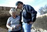 Governor Rick Perry walks with Paula Winfrey through the ashes of her mother's home which was...