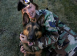 Technical Sgt. Jamie Dana plays with her German Shepherd dog, Rex, her former military working...