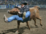 Garrett Nokes of McCook, Nebraska, gets a ride as he can't put the brakes on the steer he drew in...