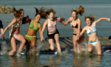 Members of the Niwot 16A girls softball team  react to jumping into the cold water Sunday morning...