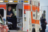 A paramedic puts on a bullet proof vest as Denver Police and SWAT team members negotiate with a...