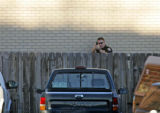 A Federal Heights police officer takes aim near the 9000 Block of Camenisch Way  where residents...