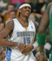 Denver Nuggets forward Carmelo Anthony holds his hand in pain after jamming his fingers in third...