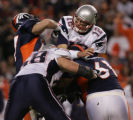 Broncos safety John Lynch (left) and defensive tackle Gerard Warren combine to put pressure on...