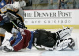 Colorado Avalanche golie David Aebischer,right,  falls on a shot on goal by Nashville Predator...