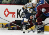 Colorado Avalanche player Brett Clark, bottom, peers at the puck through the legs of Nashville...